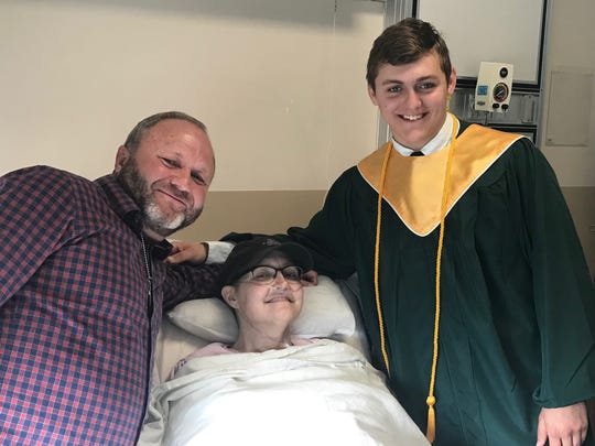 Johnny and Noah Siets pose at Marilyn's bedside during Noah's special graduation ceremony held in her hospital room.