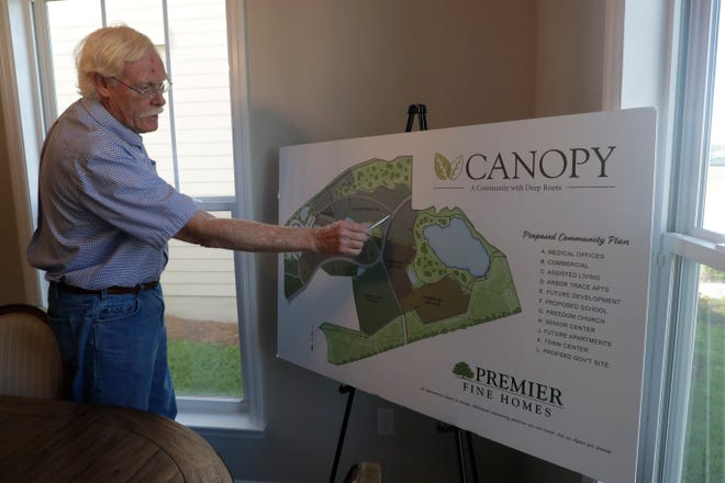 Tom Asbury, one of four developers for the the Canopy at Welaunee community, explains the different sections of the development on a map displayed inside one of the single-family model homes Thursday, May 23, 2019.