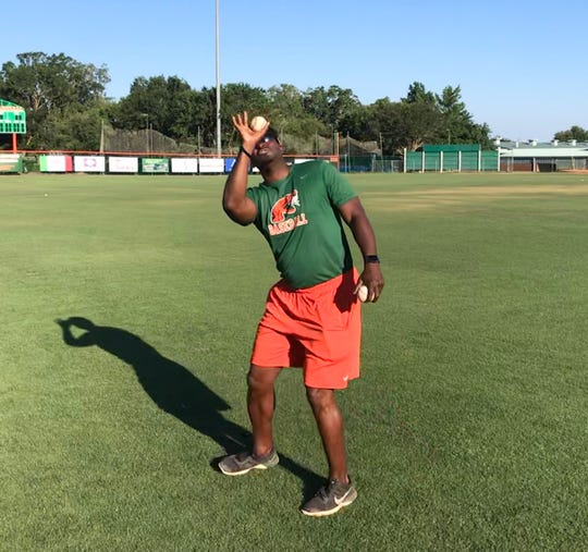 FAMU assistant baseball coach Anthony Robinson shows outfielders how to angle their glove to catch fly balls during practice on Tuesday, May 21, 2019.