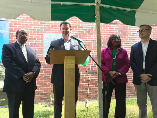 Mayor John Dailey speaks at the podium at the Jake Gaither Home Museum. Mayor Pro Tem Curtis Richardson (left), City Commissioner Diane Williams-Cox and County Commissioner Rick Minor stand beside him during his speech.