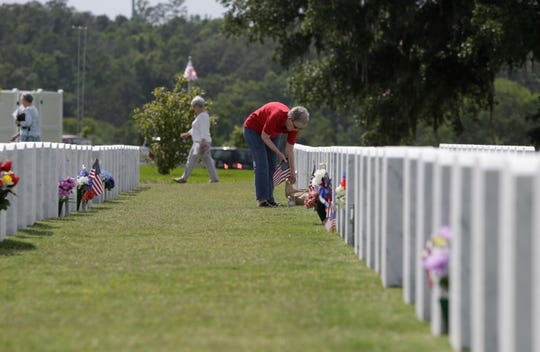 Family members place flags on the graves at Tallahassee National Cemetery Sunday in honor of Memorial Day.