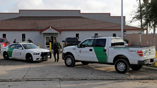 In this June 23, 2018, file photo, a U.S. Border Patrol Agent walks between vehicles outside the Central Processing Center in McAllen, Texas.