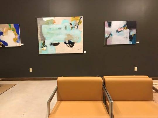 A lounge area at Whitewater Music Hall near the coat rack, by the upstairs entrance on First Street, displays visual work from a local artist.