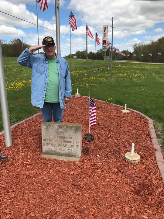 Veterans of Foreign Wars Post 2534 member Bill Haack stops for a photo and salute May 20 after placing flags at the post's meeting hall and at Forest Hill cemetery in Wisconsin Rapids.