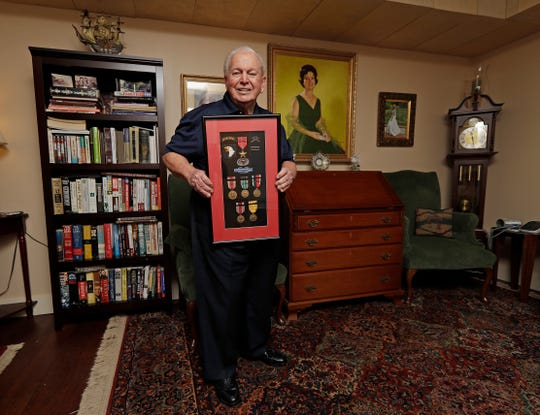 """In this Wednesday, May 22, 2019, photo, D-Day veteran Eugene Deibler poses for a photo with his medals from WWII at his home in Charlotte, N.C. """"How many people remember the Civil War? How many people will remember World War I? And now it's the same with World War II,"""" he said. """"World War II will fade away also."""" (AP Photo/Chuck Burton)"""