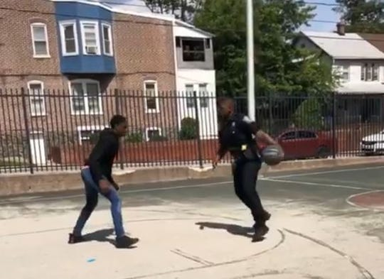 A Wilmington officer plays a game of pickup basketball on 30th Street.