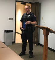 """Wisconsin Rapids Police Officer Eric Daven shows off the """"Officer of the Year"""" plaque he received Wednesday from the Wisconsin Rapids Citizens' Police Academy Alumni Association."""