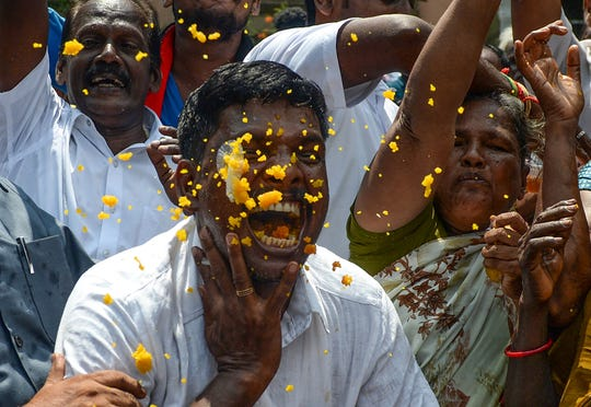 Indian members of the Dravida Munnetra Kazhagam (DMK) eat and dance as they celebrate on the vote results day for India's general election at the party headquarters in Chennai on May 23, 2019. - Indian Prime Minister Narendra Modi looked on course on May 23 for a major victory in the world's biggest election, with early trends suggesting his Hindu nationalist party will win a bigger majority even than 2014.