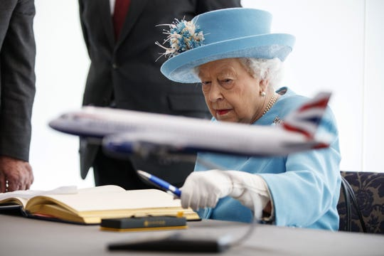 Queen Elizabeth II signs the visitor's book during her visit to the headquarters of British Airways at Heathrow, to mark the airline's centenary year, May 23, 2019 in London.