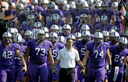 FILE - In this Sept. 27, 2014, file photo, St. Thomas coach Glen Caruso leads his team onto the field for a college football game against St. John's, in St. Paul, Minn.