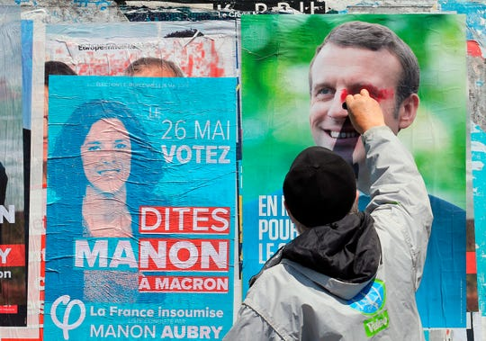 A French voter scribbles on a campaign poster of French president Emmanuel Macron in Saint-Jean-de-Luz, France, on  May 21, 2019.