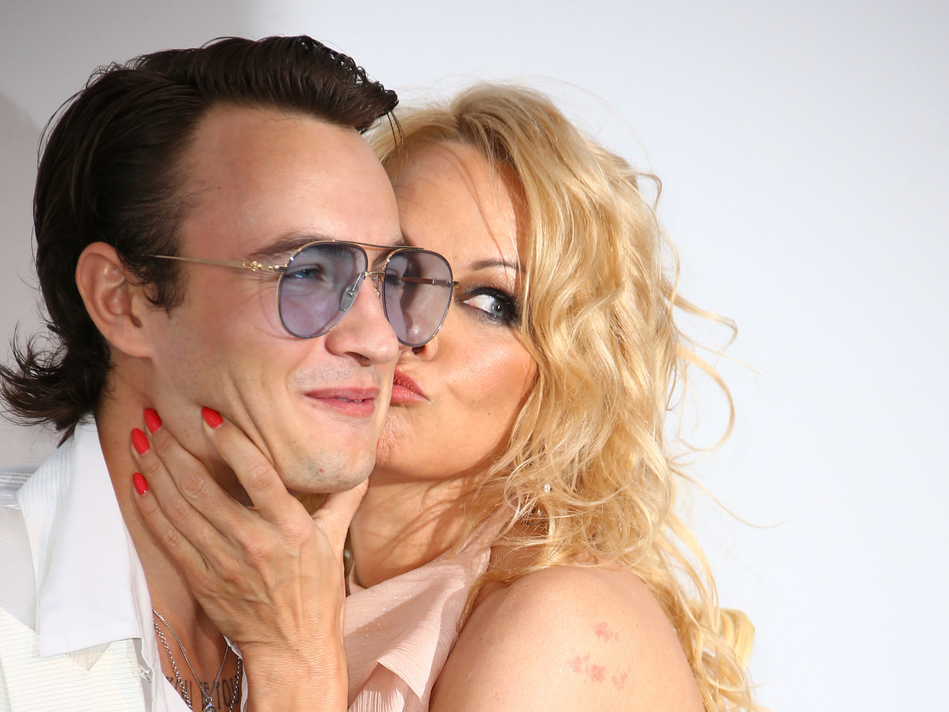 Actress Pamela Anderson, right, kisses her son Brandon Thomas Lee as they pose for photographers upon arrival at the amfAR, Cinema Against AIDS, benefit at the Hotel du Cap-Eden-Roc, during the 72nd international Cannes film festival, in Cap d'Antibes, southern France, Thursday, May 23, 2019. (Photo by Joel C Ryan/Invision/AP) ORG XMIT: LENT172