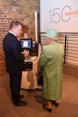 Queen Elizabeth II views a self-checkout machine during a visit to a replica of an original Sainsbury's stores in Covent Garden in London on May 22, 2019 to mark the grocery company's 150th anniversary.