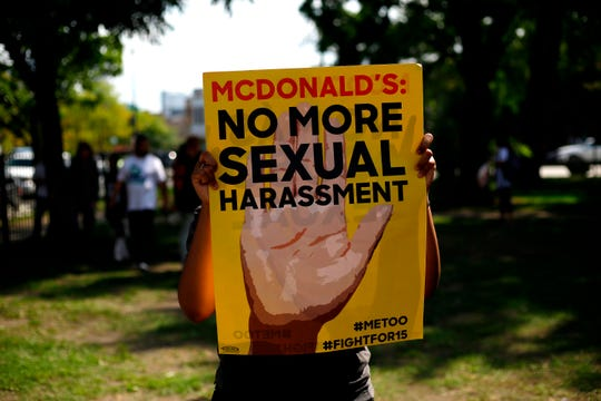 In this file photo taken on September 18, 2018, a McDonald's employee holds a sign during a protest against sexual harassment in the workplace, in Chicago, Illinois. - McDonald's workers filed dozens of  new sexual harassment charges against the fast food giant, advocates said on May 21, 2019, escalating a years-long battle for unionization in the US and stronger worker protections.