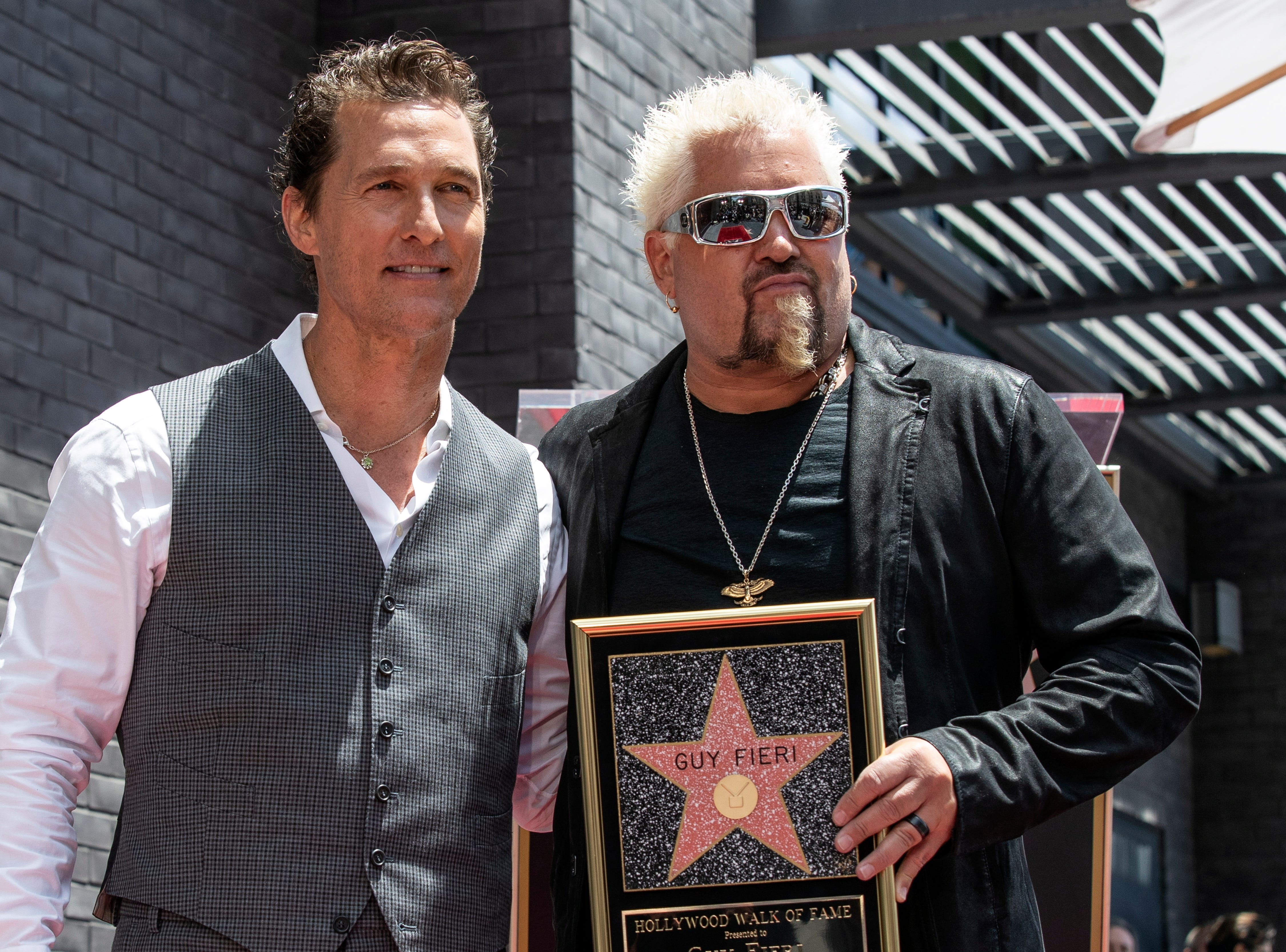 Chef and TV personality Guy Fieri, right, poses for a photograph with US actor Matthew McConaughey after he unveiled his star on the Hollywood Walk of Fame in Hollywood, Calif. on May 22, 2019. The star, the 2,664th and third to be given to a chef, was dedicated in the category of television.