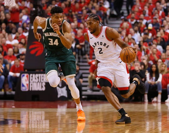 Kawhi Leonard (2) dribbles as Milwaukee Bucks forward Giannis Antetokounmpo (34) gives chase during Game 4 of the Eastern Conference final.