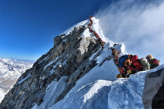 This handout photo taken on May 22, 2019, and released by climber Nirmal Purja's Project Possible expedition shows heavy traffic of mountain climbers lining up to stand at the summit of Mount Everest.