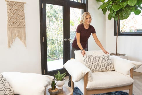 Reality TV star Christina Anstead fixes a decorative pillow.