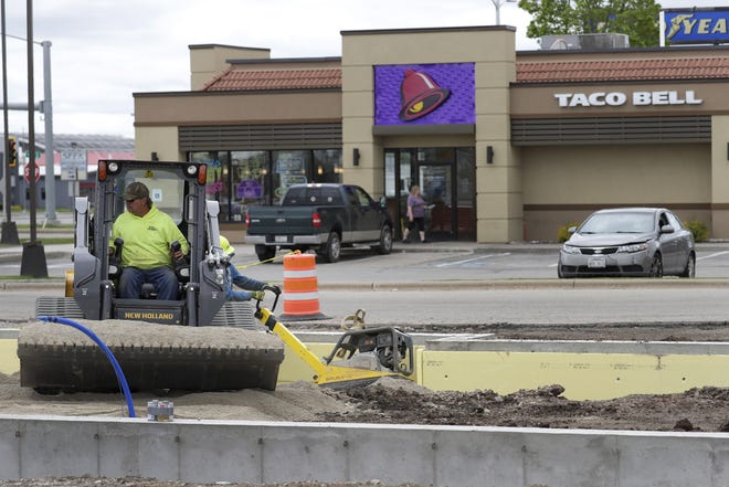 An employee with Tom Van Handel Corp. backfills the foundation of the new Popeyes Louisiana Kitchen along W. College Avenue in Appleton.