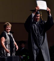 Noeh Rodriguez holds his diploma high after receiving it from Mignon Lawson in the Abilene High School auditorium Thursday. Rodriguez was selected as Student of the Year.