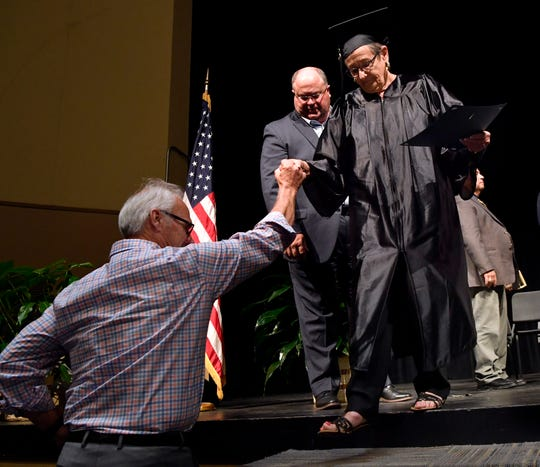Brenda Bristow is assisted by Royce Curtis as she exits the stage in the Abilene High School auditorium after receiving her GED during Thursday's graduation ceremony for West Central Texas Adult Education. This was the program's largest class, more than 70 graduates with Bristow at 75 the most senior of the seniors.