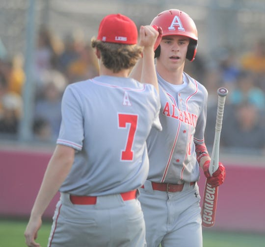 Albany's Blaine Kayga, right, fist-bumps Cade Neve after scoring a run in Game 1 of a Region I-2A semifinal baseball series Thursday, May 23, 2019, at Hermleigh Cardinal Field.