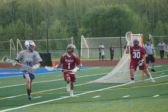 Owego's Cole Taylor is pursued by Johnson City's D.J. Peer as Wildcats goalie Brittan Stimak watches in the first half of Thursday's Section 4 Class C final at Owego. The Indians won, 14-11.