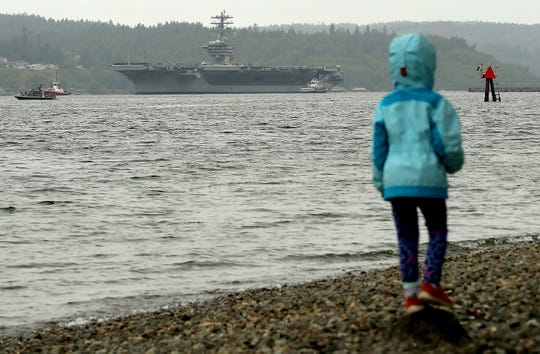 Lucy Bilibin, 5, stands atop a rock in the foreground as the USS Nimitz passes Bachmann Park in Manette on Friday. The Bremerton-based aircraft carrier departed for the first time following a lengthy maintenance period at Puget Sound Naval Shipyard. Lucy's father, Alex, is a chief aboard the ship.