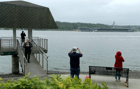 Onlookers line the shore as the USS Nimitz passes Bachmann Park in Manette on Friday.