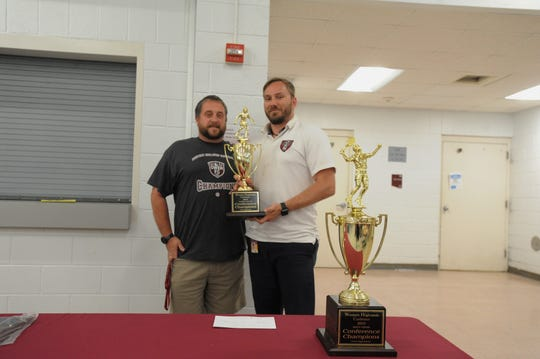 Owen Warlassies head coach David Fiest, right, and assistant coach Ray Nightingale collect the soccer team's second consecutive Western Highlands Conference championship trophy on May 21. The Warlassies, who advanced to the third round of the playoffs in 2018 and 2019, are 20-0 in the conference over the past two seasons.