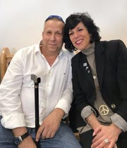 Betsy Fischer, owner of Betsy Fischer's Groove Lounge in Voorhees, visits with Gadi Yarkoni, who survived a mortar attack during the 2014 Gaza-Israel conflict. Fischer will close her business at the end of June to focus on writing Yarkoni's biography.