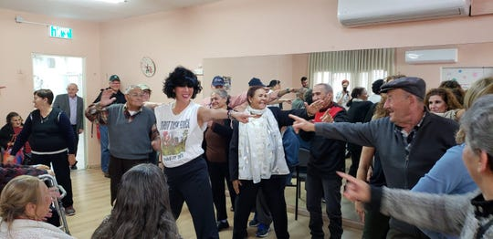 Betsy Fischer enjoys a light moment with senior citizens in Israel as part of her volunteer work with the Jewish National Fund.