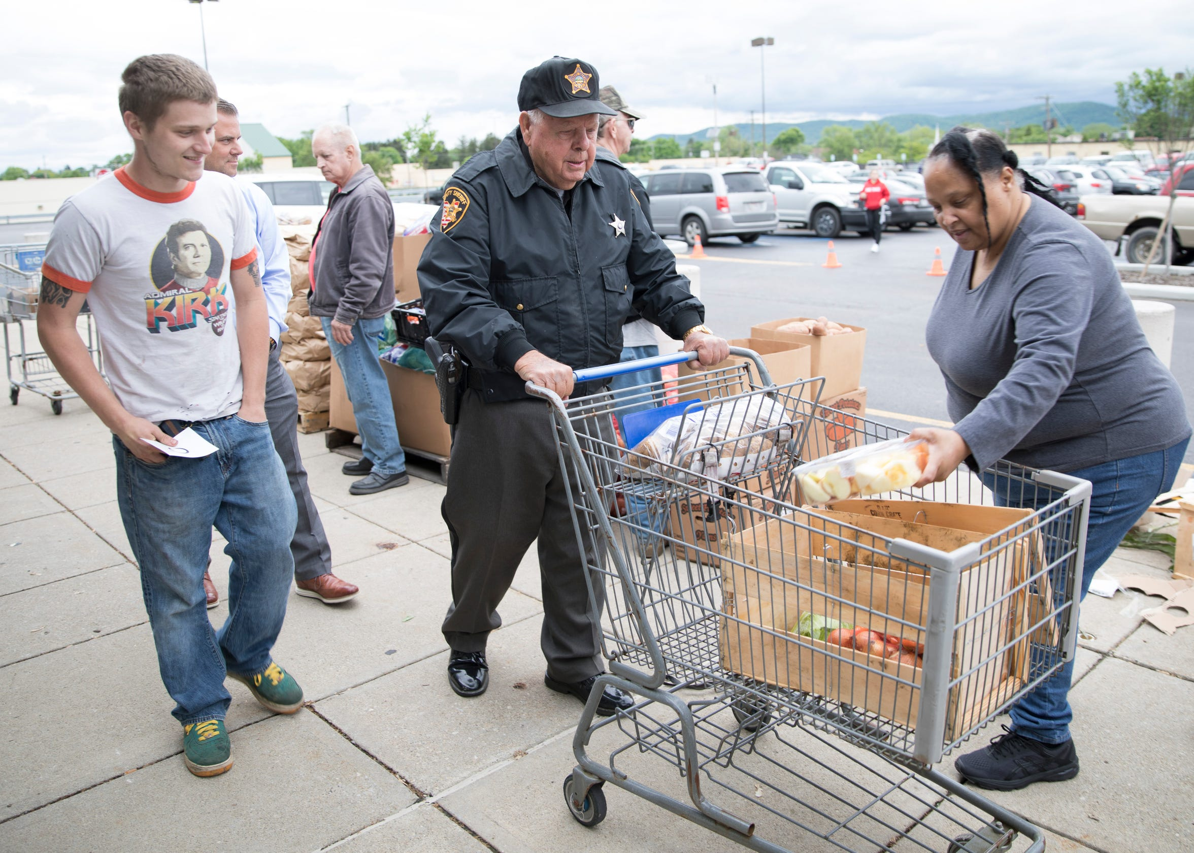 Doug Ray likes to stay active and help food market visitors like Buddy Staley get their food and assist them to their car.