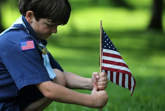 Sullivan Vehorn, 8, of West Chester Township, plants flags along with members of Cub Scout Pack 260 from St. Gabriel Parish in Glendale, Thursday, May 23, 2019, at Spring Grove Cemetery in Cincinnati. The pack planted more than 1,000 American flags on the graves of those soldiers interred in the historic Civil War section of the cemetery.