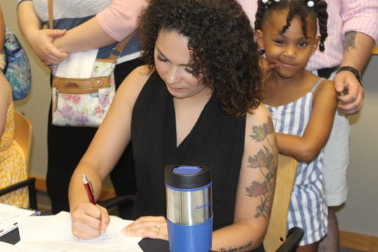 Lina Horton, one of 40 new residents in Montgomery County's first Early Learning Teacher Residence program, signs his contract on May 24, 2019.