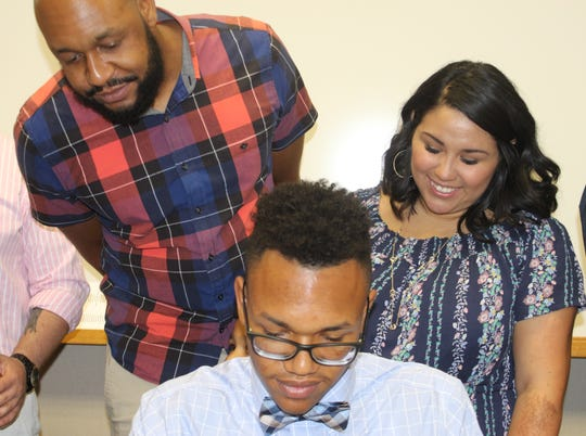 Malachi Johnson, one of 40 new residents in Montgomery County's first Early Learning Teacher Residence program, signs his contract on May 24, 2019.
