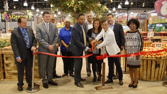 Linden Mayor Derek Armstead helps cut the ribbon at the grand opening of the new SuperFresh store in Linden.