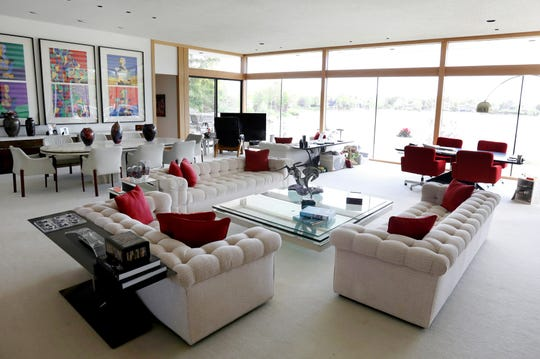 The huge greatroom faces the lake through walls that jut out to make three sides of glass. It includes the formal dining area, a large conversation area, a television corner and a table for casual use. The 9,000-square-foot house is in a neighborhood of a half dozen homes built far back from the road on the shoreline of a former estate.