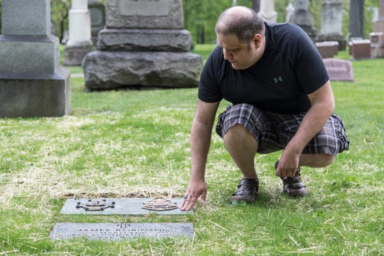 Elijah Shalis of secretary for the Michigan Society Sons of the American Revolution poses for a photo next to James Robinson's headstone at Elmwood Cemetery in Detroit, Friday, May 24, 2019. Rev. PVT. James Robinson died in 151 years ago. The Michigan Society Sons of The American Revolution is hosting a patriot grave marking ceremony for him on June 22, 2019 at the cemetery.