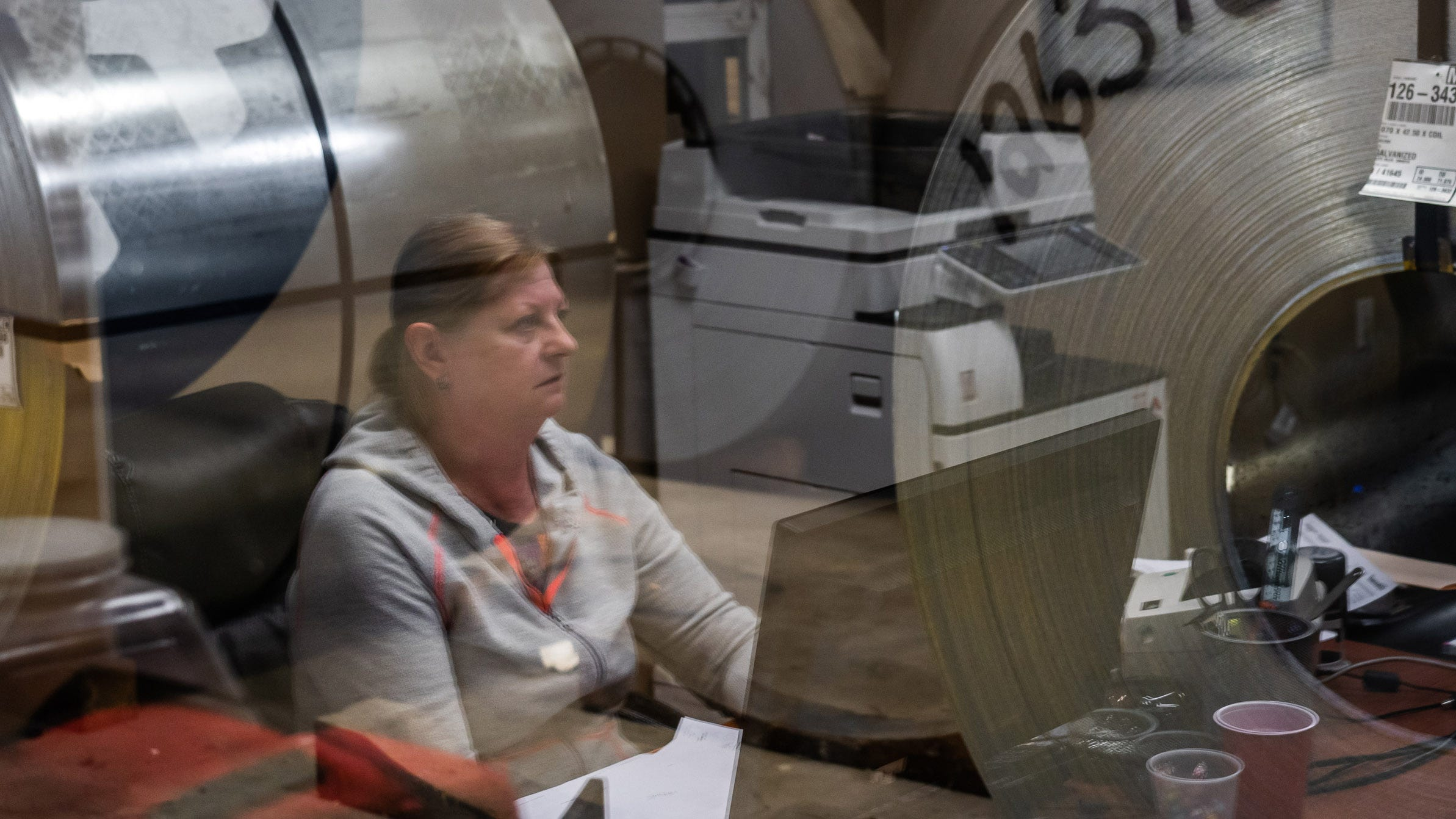 Hascall Steel Company employee Sharon Lathrop talks in April about the change in her route getting to and from work due to the widening of I-94 in Detroit, while reflected on her office window as rolls of steel sit inside the business.