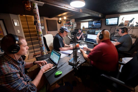Producers, engineers, and talent participate in a taping of the Drew & Mike podcast in a recording studio in the basement of Drew Lane's home in Ferndale.