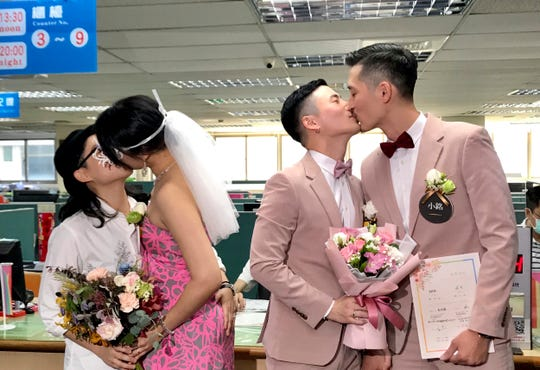 Two same-sex couples seal their legal marriage with a kiss at the registration office in Xingyi District in Taipei, Taiwan, Friday, May 24, 2019
