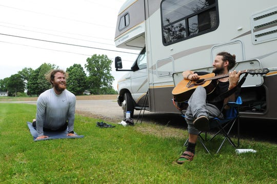Mike Posner does yoga while his friend, Julian Roy, strums a tune during Posner's walk across America.