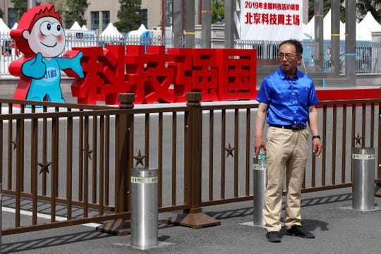 "A man stands near the Chinese characters for ""Science and Technology strengthens the Country"" outside an exhibition the National Science and Technology Week held at the Military Museum in Beijing on Friday, May 24, 2019."