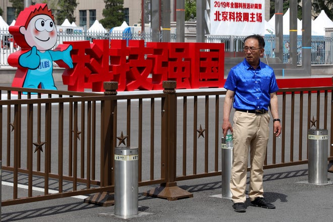 """A man stands near the Chinese characters for """"Science and Technology strengthens the Country"""" outside an exhibition the National Science and Technology Week held at the Military Museum in Beijing on Friday, May 24, 2019."""