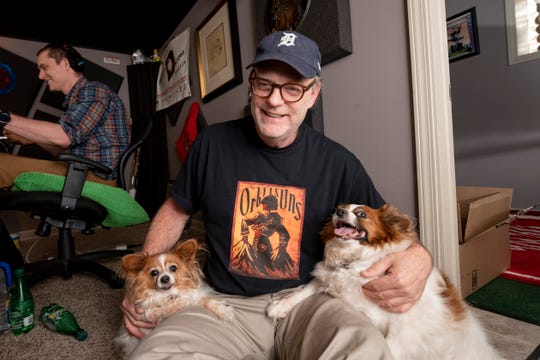 Drew Lane sits with his two dogs Layla, left, and Maggs during a break in a taping of the Drew & Mike podcast in the recording studio in his basement in Ferndale.