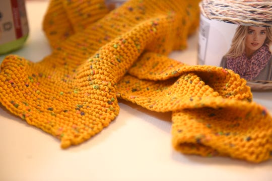 A yellow  knitted scarf by Gregg Burrell at her Highland Park studio.
