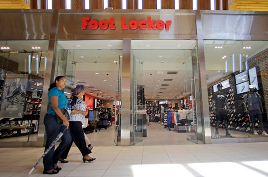In this Aug. 22, 2017 file photo, shoppers walk past a Foot Locker store in Hialeah, Fla. Foot Locker Inc. on Friday, May 24, 2019, reported fiscal first-quarter earnings of $172 million. The New York-based company said it had profit of $1.52 per share. Earnings, adjusted for non-recurring costs, were $1.53 per share.