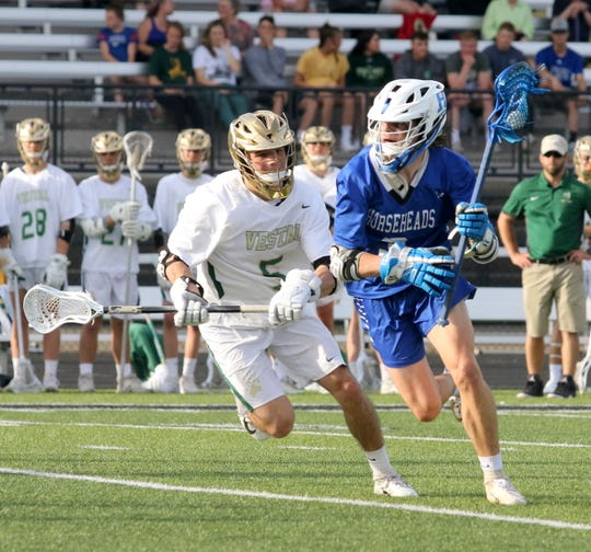 Dawson Felenchak of Horseheads moves up the field with the ball as J.P. Sacco of Vestal defends during the Section 4 Class B boys lacrosse final May 23, 2019 at Corning Memorial Stadium.