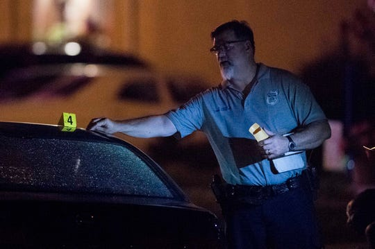 EPD Detective Phil Luecke collects a bullet casing from the top of a car in the 1200 block of Madison Avenue on Evansville's South Side after a shooting that sent one to the hospital Thursday, May 23, 2019.